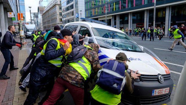 Göstericiler Brüksel'de polis minibüslerini ateşe verdi.
