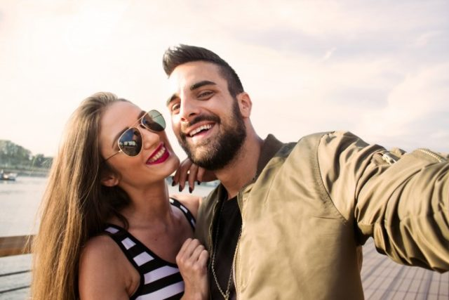 capturing-bright-moments-joyful-young-loving-couple-making-selfie-camera-while-standing-outdoors_1212-816