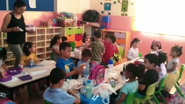 Okul müdürü çocuğa bakıyor, öğretmen de öğrencilere ders veriyor