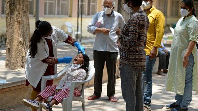 Hindistan'da bir çocuğa koronavirüs testi yapılıyor