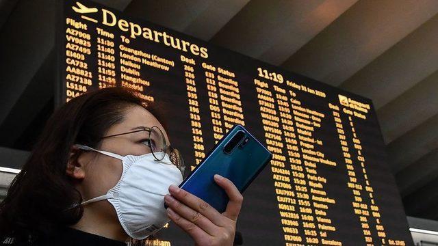 Solunum maskesi takan bir yolcu, 31 Ocak 2020'de Roma'nın Fiumicino havaalanında kalkış panosunun yanında akıllı telefonuyla konuşuyor
