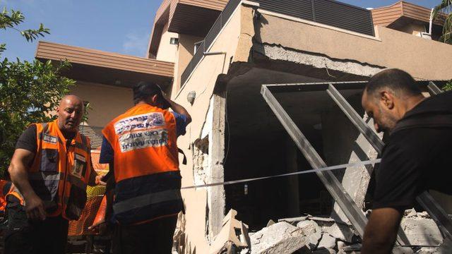 Aşkelon'da Gazze'den atılan bir roketin isabet ettiği evdeki İsrailli kurtarma görevlileri.