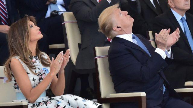 Donald Trump ve First Lady Melania Trump, Bastille Günü törenlerinde geçiş yapan savaş uçaklarını seyrederken.