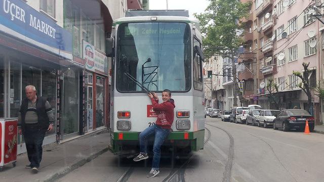 Bursa'da tramvayın arkasında tehlikeli yolculuk