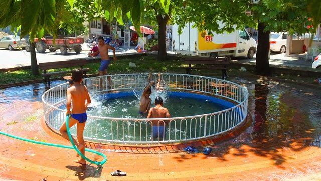 Bigadiç'te çocuklar süs havuzunda serinliyor