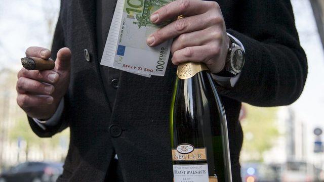 elinde para ve şampanya şişesi tutan adam.